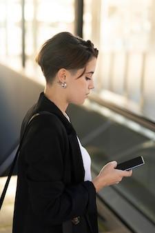Стильная женщина проверяет свой телефон