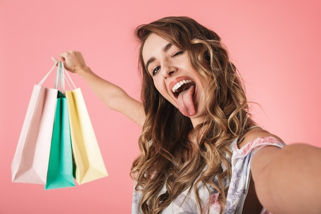 Stylish woman in dress holding colorful shopping bags and taking selfie, isolated on pink