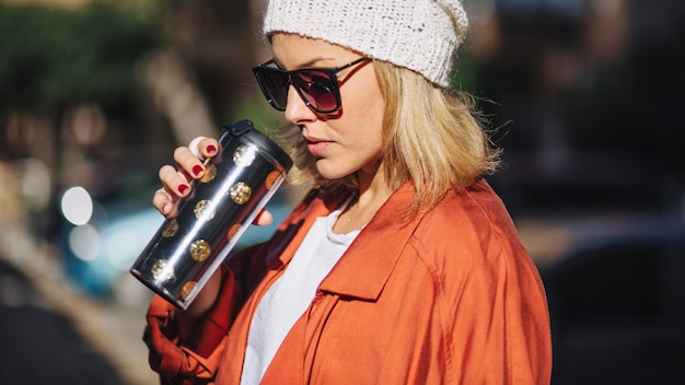 Stylish woman drinking hot beverage on street
