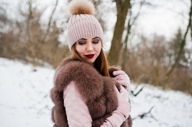 Stylish woman in fur coat and headwear at winter forest.