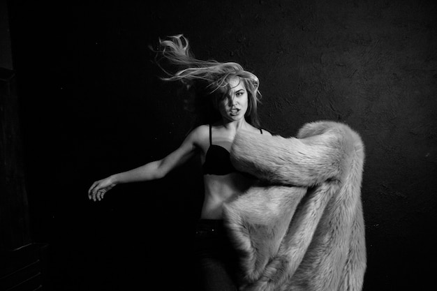 Stylish woman in fur coat sharp movement studio light