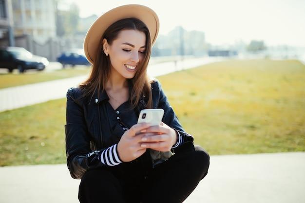 黒い服を着て寒い晴れた夏の日に市の湖の近くの公園に座っているスタイリッシュな女性の女の子