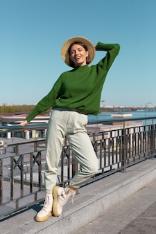 Stylish woman in green casual sweater and hat outdoor on bridge with river view enjoys summer sunny day