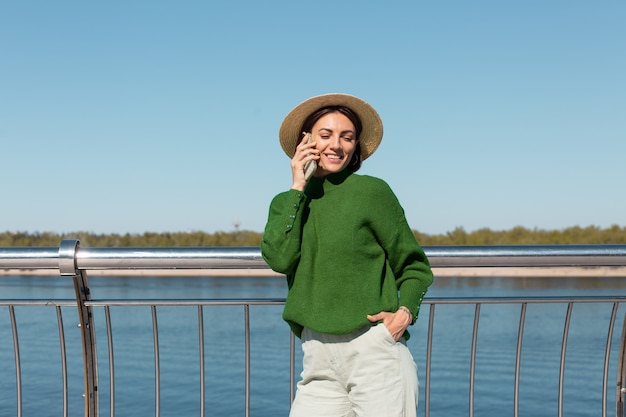 Stylish woman in green casual sweater and hat outdoor on bridge with river view at warm sunny summer day talks on mobile phone