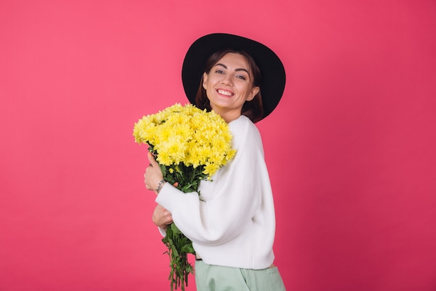 Stylish woman in hat and casual white sweater on pink red wall