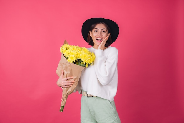 Stylish woman in hat and casual white sweater on red wall
