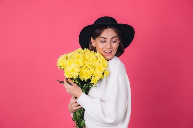 Donna alla moda in cappello e maglione bianco casual sulla parete rossa