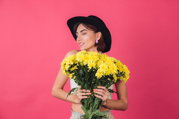 Stylish woman in hat, hugging large bouquet of yellow asters, spring mood, calm smiling isolated space