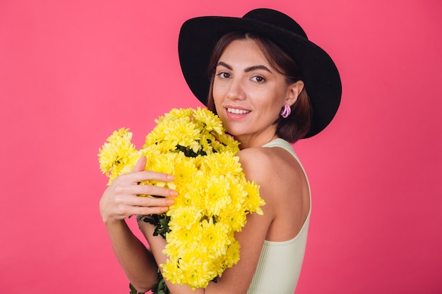 Stylish woman in hat, hugging large bouquet of yellow asters, spring mood, happy emotions isolated space