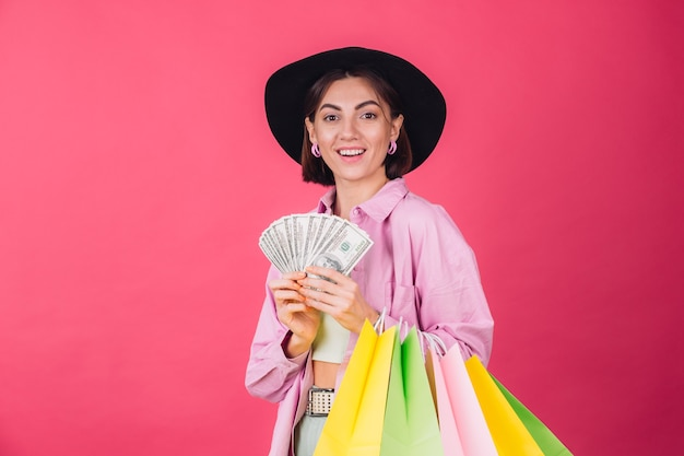 Donna alla moda in cappello sulla parete rossa rosa