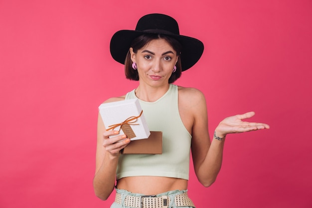 Stylish woman in hat on pink red wall