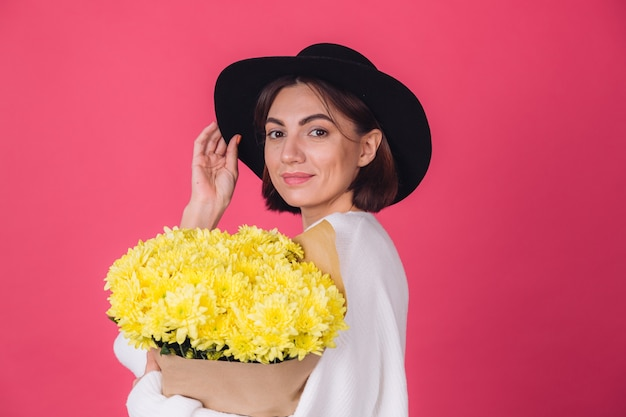 Stylish woman in hat on red wall