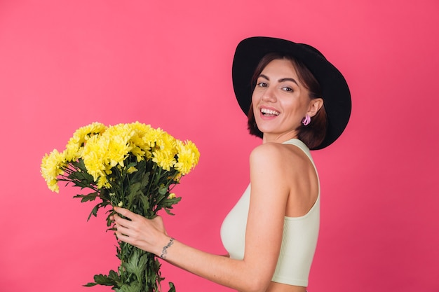 Stylish woman in hat, sips to left large bouquet of yellow asters, spring mood, happy emotions isolated space