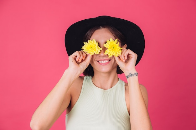 Stylish woman in hat, smile on face cover eyes with yellow asters, spring mood, happy emotions isolated space