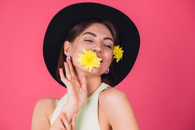 Stylish woman in hat, smiling with two yellow asters, cute hold one flower in mouth spring mood, happy emotions isolated space