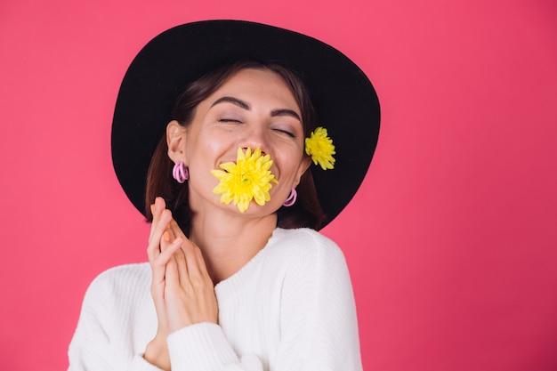 Donna alla moda in cappello, sorridente con due astri gialli, carino tenere un fiore in bocca umore primaverile, spazio isolato di emozioni felici