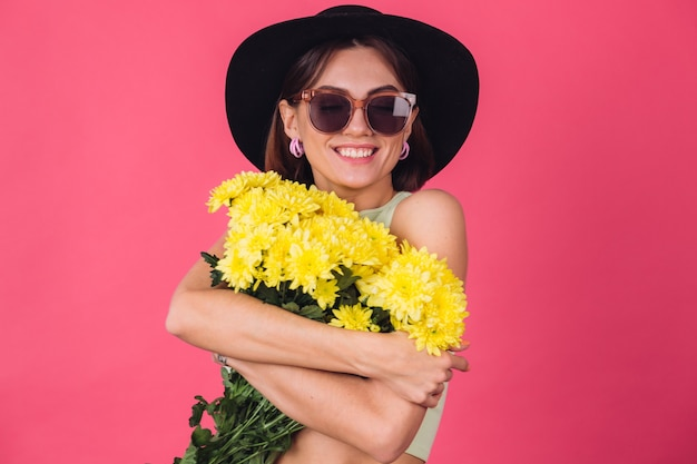 Stylish woman in hat and sunglasses, hugging large bouquet of yellow asters, spring mood, calm smiling isolated space