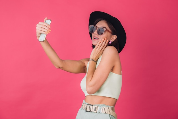 Stylish woman in hat and sunglasses on pink red wall