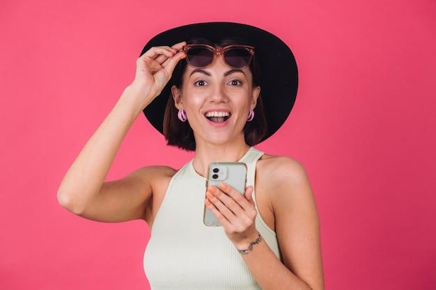 Donna alla moda in cappello e occhiali da sole sulla parete rossa rosa