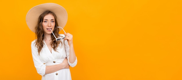Stylish woman in hat and sunglasses posing on a yellow