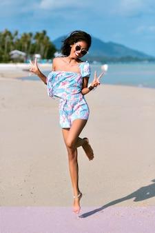 Donna alla moda divertendosi sulla bellissima spiaggia tropicale