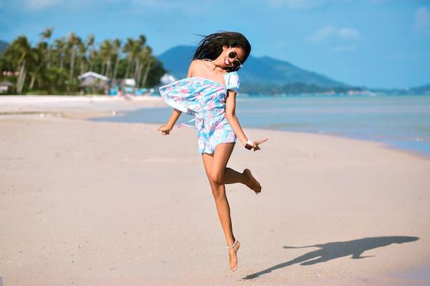 Стильная женщина веселится на красивом тропическом пляже