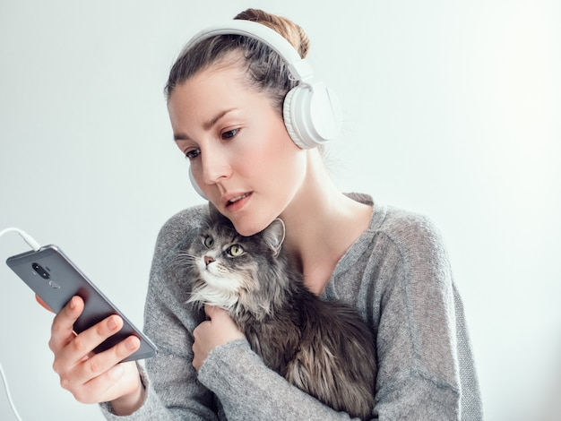 Stylish woman in headphones and with her kitten
