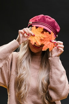 Stylish woman hiding her face behind dry maple leaves against black background