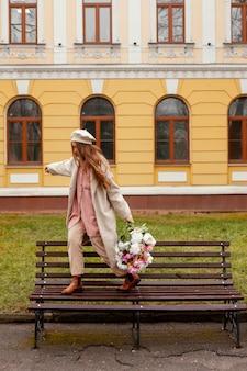 벤치에 봄에 야외에서 꽃의 꽃다발을 들고 세련된 여자