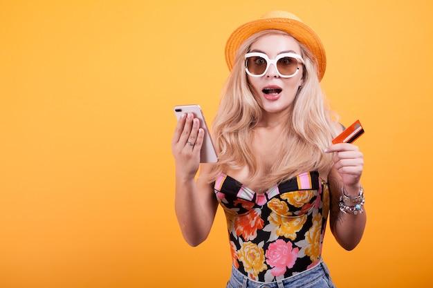 黄色の背景の上のスタジオでクレジットカードと電話を保持しているスタイリッシュな女性