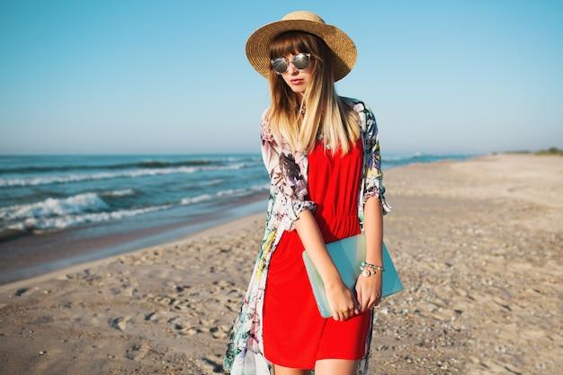 スタイリッシュな女性のラップトップを押しながら熱帯のビーチの上を歩く