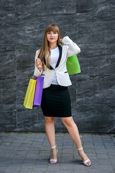 ショッピングからちょうど服で色のパッケージを保持しているスタイリッシュな女性