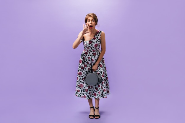 スタイリッシュな女性がハンドバッグを持って叫びます。長くカラフルなドレスと黒のスタイリッシュなかかとでファッショナブルなかわいい女の子は灰色のハンドバッグを保持します。