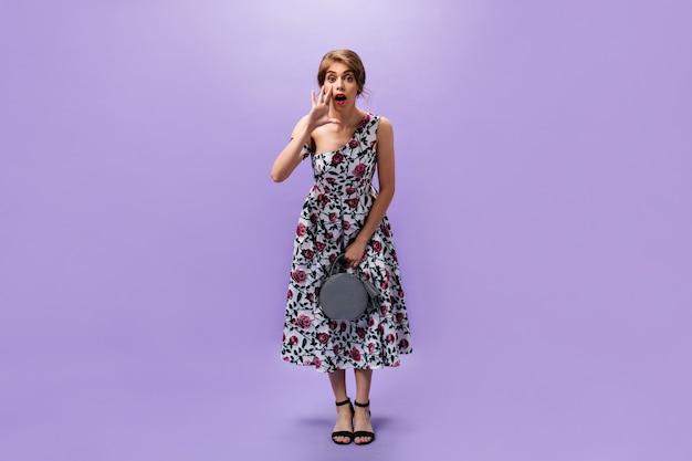 Stylish woman holds handbag and shouts. fashionable pretty girl in long colorful dress and black stylish heels holds grey handbag.