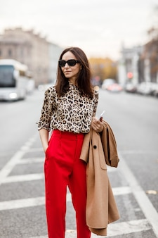 베이지 색 코트와 빨간 바지에 세련 된 여자