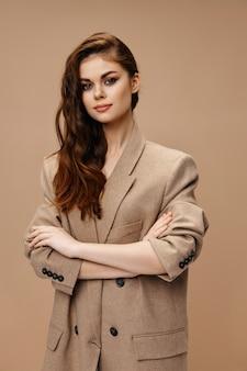 코트를 입은 세련된 여성이 베이지색 배경 위에 팔짱을 꼈습니다. 고품질 사진
