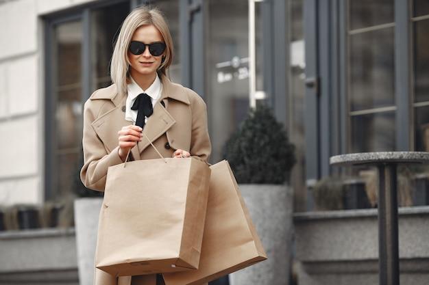 Стильная женщина в весеннем городе с сумками