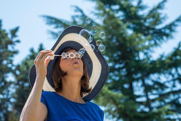 泡を吹いて麦わら帽子でスタイリッシュな女性