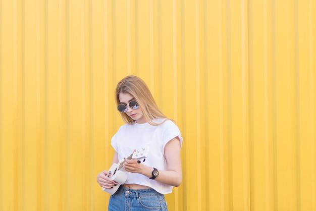 흰색 티셔츠에 세련 된 여자는 노란색 벽에 서 우쿨렐레를 재생합니다. 귀여운 소녀 놀이 우쿨렐레