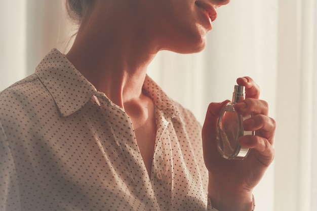 お気に入りの香水のボトルを吹きかけるブラウスのスタイリッシュな女性が自宅でクローズアップ。