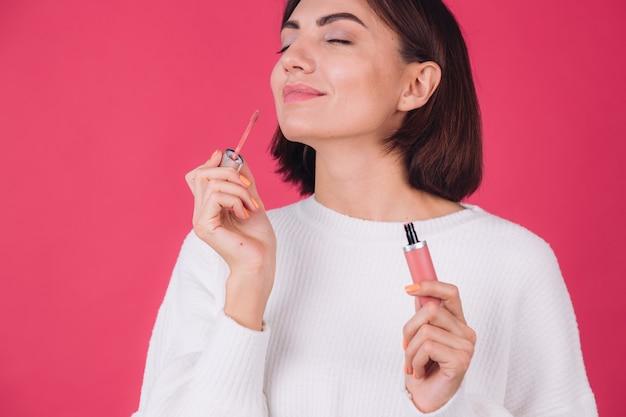Стильная женщина в повседневном белом свитере на розовой красной стене