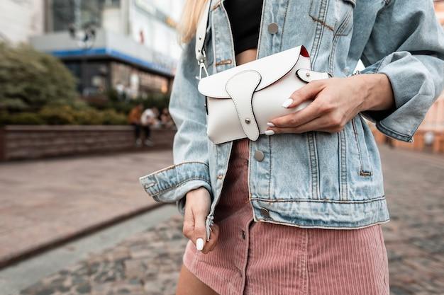 거리에 흰색 가죽 핸드백이 달린 데님 재킷과 분홍색 치마를 입은 세련된 여성