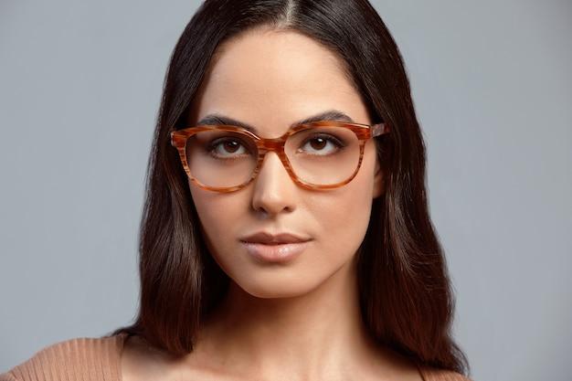 メガネのスタイリッシュな女性、灰色の背景にスタイリッシュなメガネのビジネス女性のファッションの肖像画、メガネの広告バナー、コピースペース
