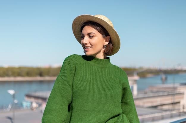 緑のカジュアルなセーターと帽子のスタイリッシュな女性は、川の景色を望む橋の上で屋外で夏の晴れた日を楽しんで、陽気で、楽しく、幸せでポジティブな雰囲気だけを楽しんで、太陽光線をキャッチします
