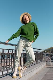Стильная женщина в зеленом повседневном свитере и шляпе на мосту с видом на реку наслаждается летним солнечным днем