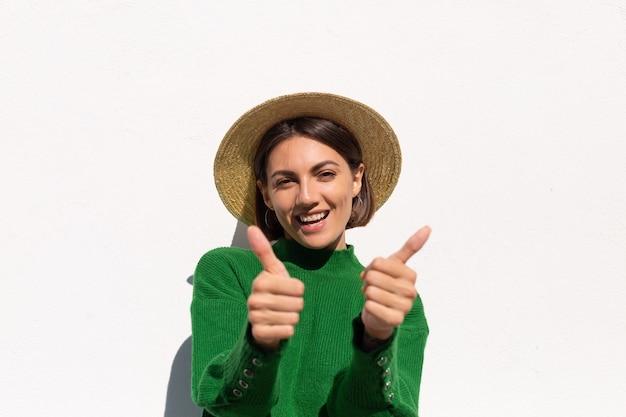 緑のカジュアルなセーターと白い壁の屋外の帽子のスタイリッシュな女性は陽気で、楽しく、興奮して暑い夏の日を楽しんでいます