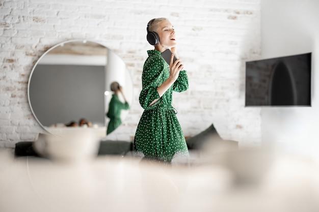 녹색 드레스를 입은 세련된 여성은 집 거실에서 헤드폰과 휴대폰 춤으로 음악을 즐깁니다. 안락한 생활과 여가 시간 개념