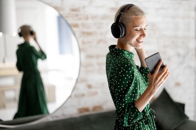 녹색 드레스를 입은 세련된 여성은 집 거실에서 헤드폰과 휴대폰 춤으로 음악을 즐깁니다.