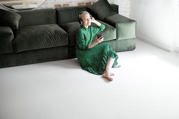 녹색 드레스를 입은 세련된 여성은 집에서 소파 근처 바닥에 앉아 헤드폰과 휴대폰으로 음악을 즐깁니다.