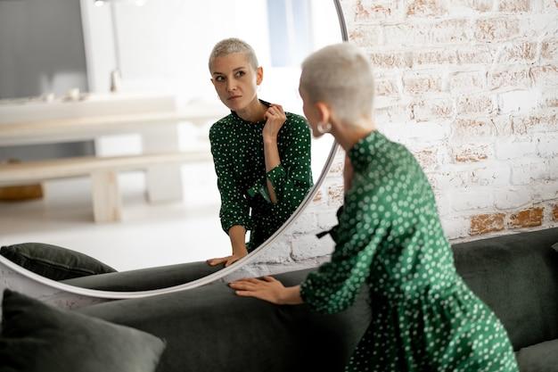 緑のドレスを着たスタイリッシュな女性が鏡で顔を見て、外出の準備をしています。女性のスタイルと美しさの概念